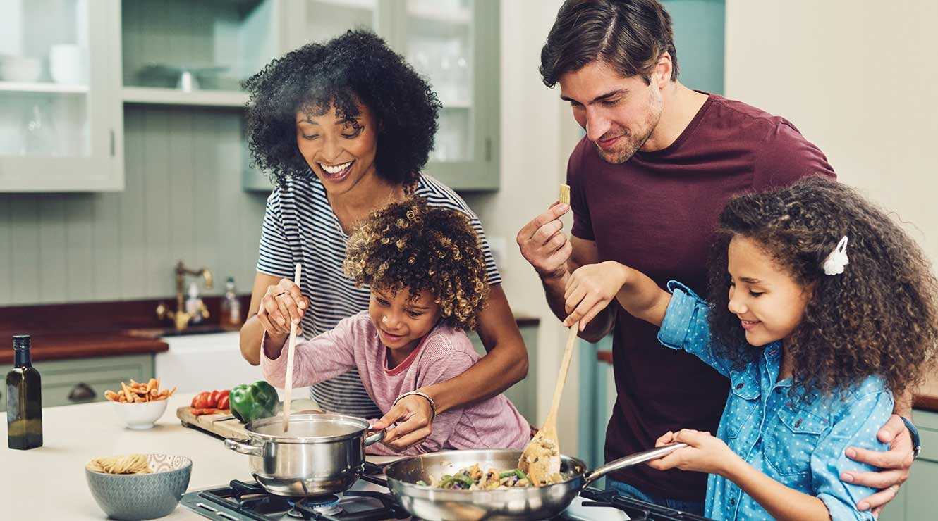 Picture of family making dinner together.