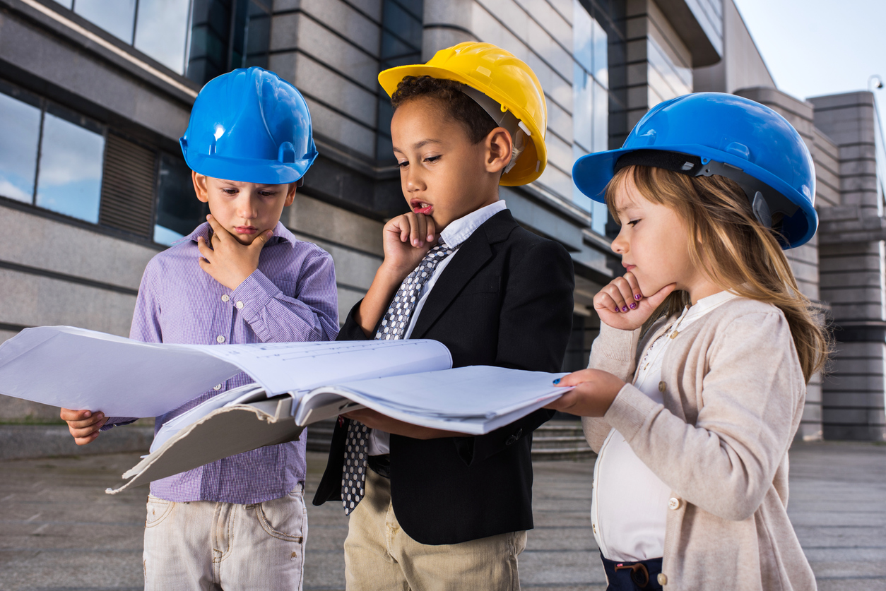 Image of three children in hardhats looking at plans.